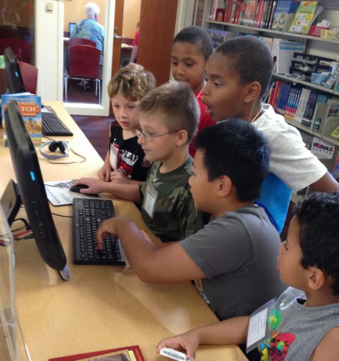 Children gathered around a computer station